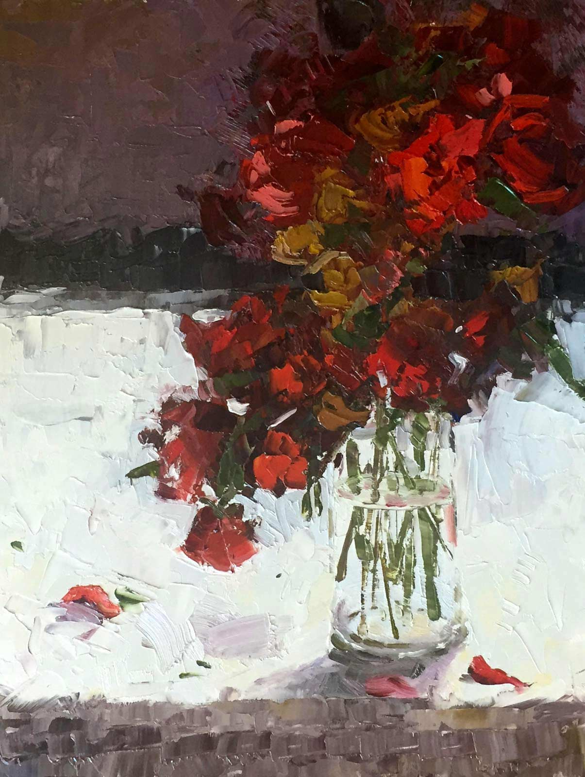 An original oil painting of a bouquet of vibrant red flowers with fallen petals.